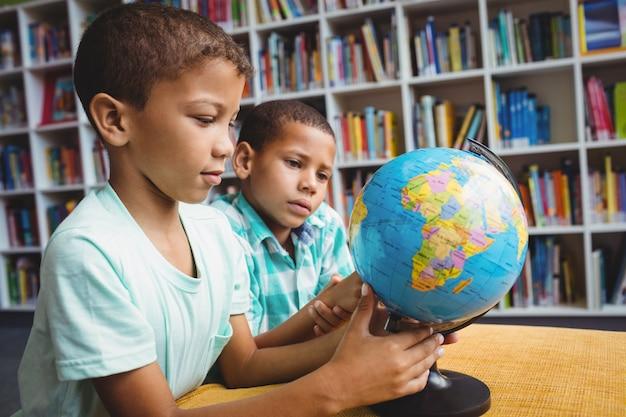 Chicos estudiando el globo