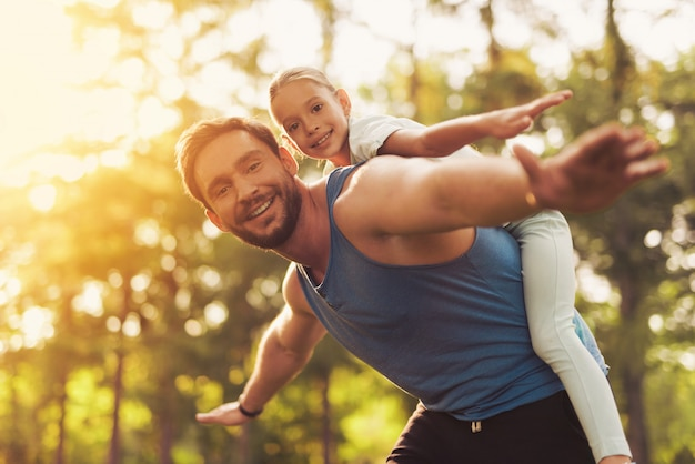 Chicos fool alrededor. hombre montando a niña en los hombros.