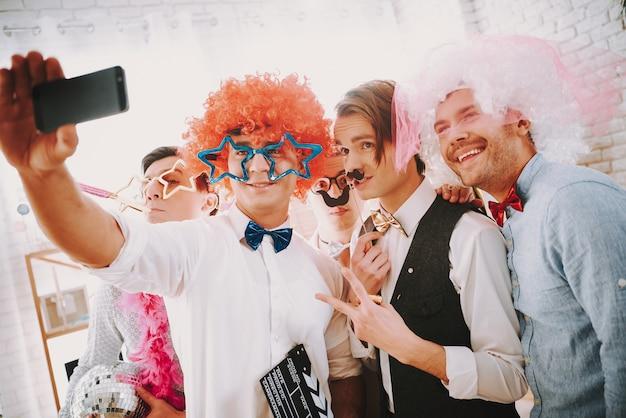 Chicos gay están tomando selfie en el teléfono en la fiesta