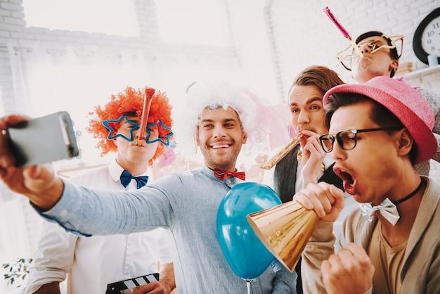 Chicos gay en pajaritas tomando selfie en el teléfono en casa.