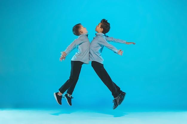 Chicos graciosos lindos saltando y golpeando las barrigas