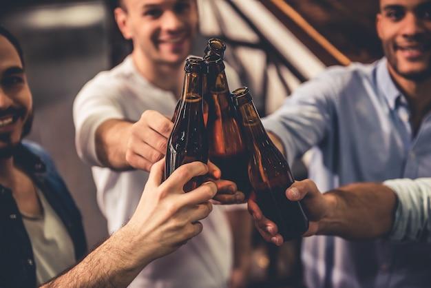 Chicos guapos tintinean botellas de cerveza y sonríen.