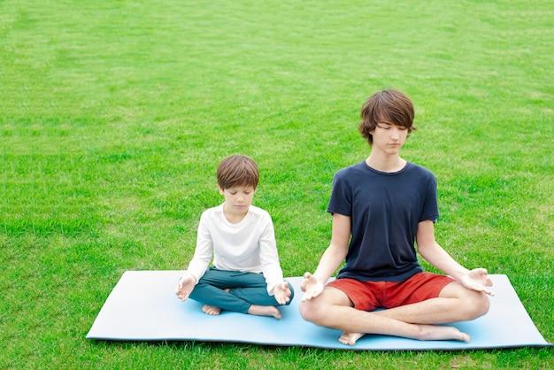 Chicos jóvenes haciendo yoga al aire libre sobre la verde hierba
