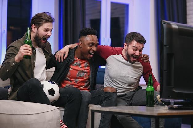 Chicos jóvenes multirraciales alegres y agradables que animan a su equipo de fútbol favorito con gritos y manos en alto mientras ven un juego deportivo en la televisión