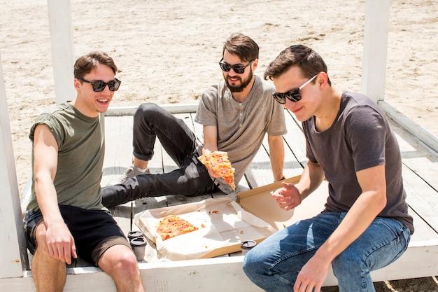 Chicos jóvenes con pizza descansando en la playa