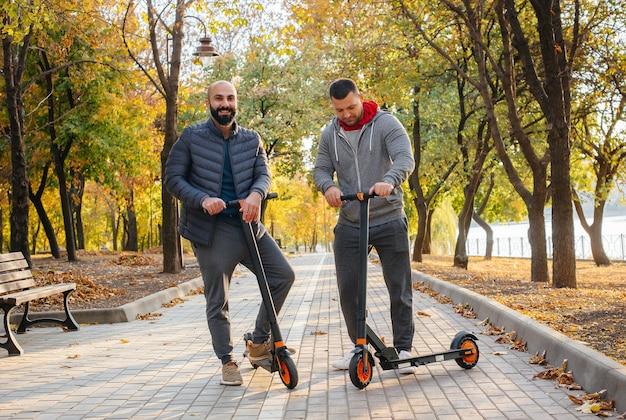 Chicos jóvenes viajan en el parque en un scooter eléctrico en un cálido día de otoño. caminar en el parque.