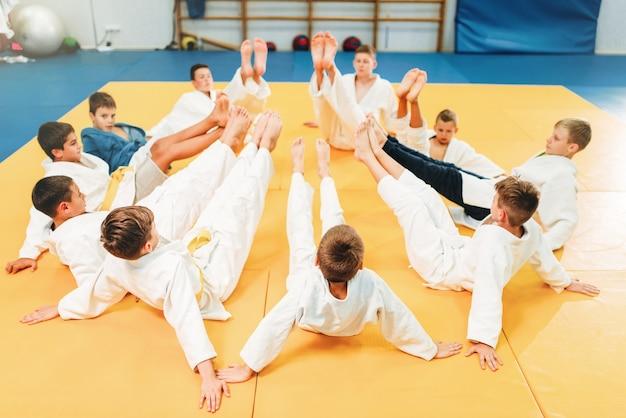 Chicos en kimono entrenando en el suelo, judo infantil. jóvenes luchadores en gimnasio, arte marcial para la defensa