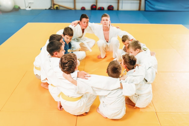 Chicos en kimono sentados en el suelo, entrenamiento de judo para niños. jóvenes luchadores en gimnasio, arte marcial para la defensa