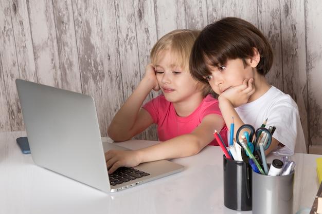 Chicos lindos en camisetas de color rosa y blanco con portátil gris sobre la mesa con bolígrafos sobre fondo gris