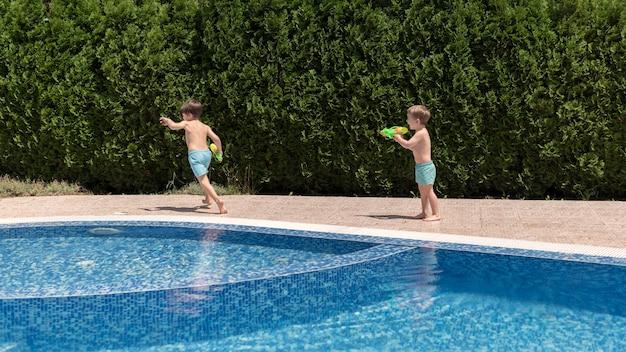 Chicos en la piscina jugando con pistola de agua