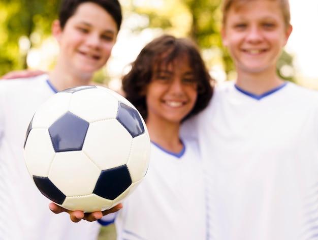 Chicos en ropa deportiva sosteniendo una pelota de fútbol.