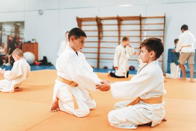 Chicos en uniforme practican artes marciales.