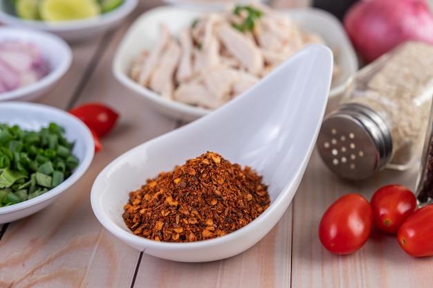 Chile de cayena en una cuchara blanca, tomate colocado sobre una mesa de madera.