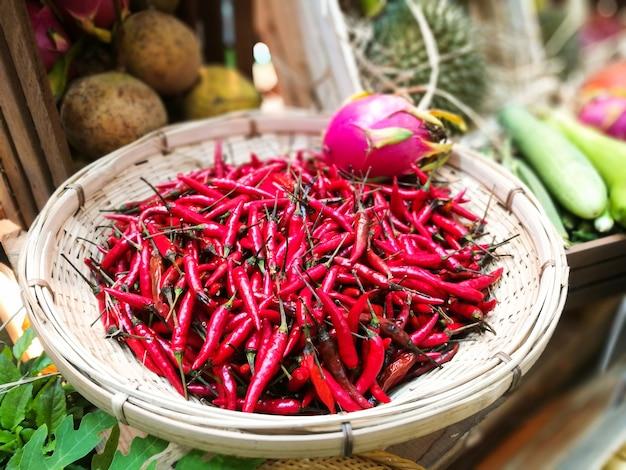Chiles rojos en bandeja de mimbre para navegar en el mercado tailandés