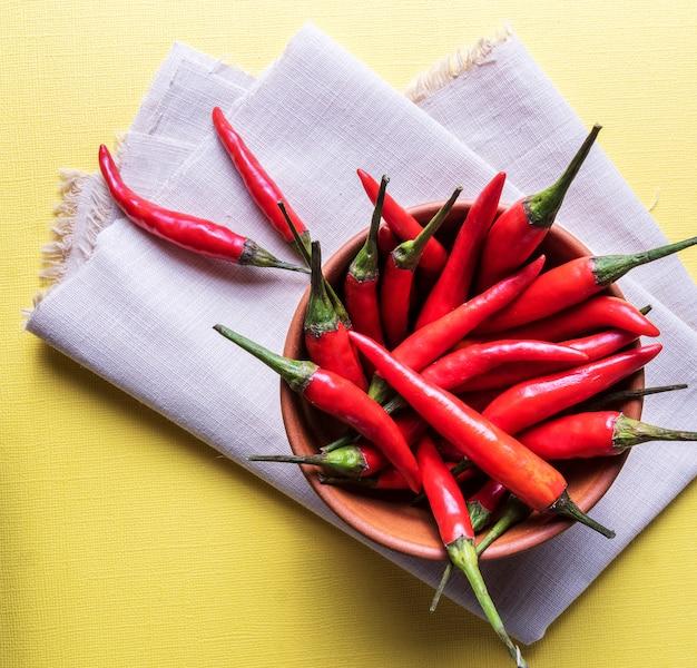 Chiles rojos maduros en un tazón sobre superficie amarilla