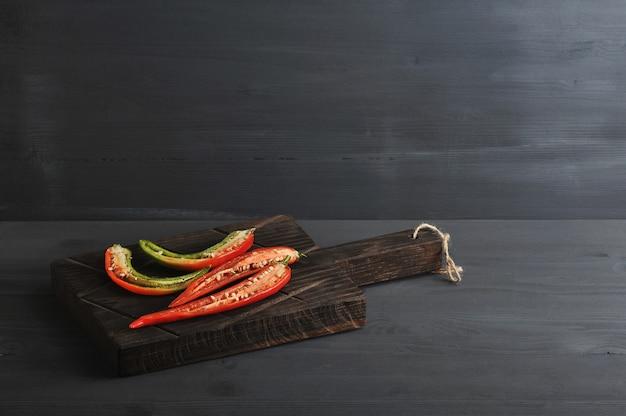 Chiles rojos y verdes cortados por la mitad en una tabla de madera