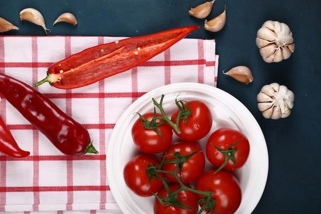 Chiles, tomates y ajos sobre una mesa.