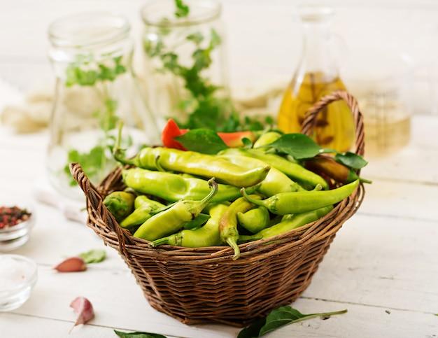 Chiles verdes en una cesta en una mesa blanca.
