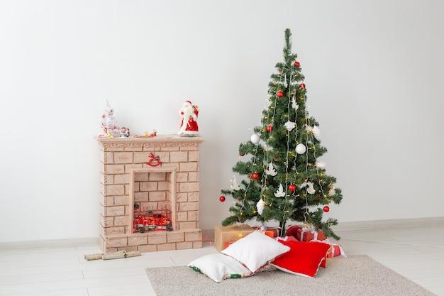 Chimenea y árbol de navidad con regalos en salón.