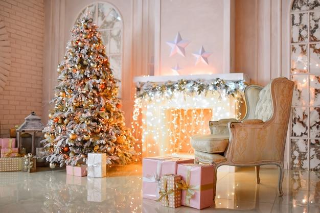 Chimenea blanca decorada con guirnalda amarilla y árbol de navidad de pie por ella