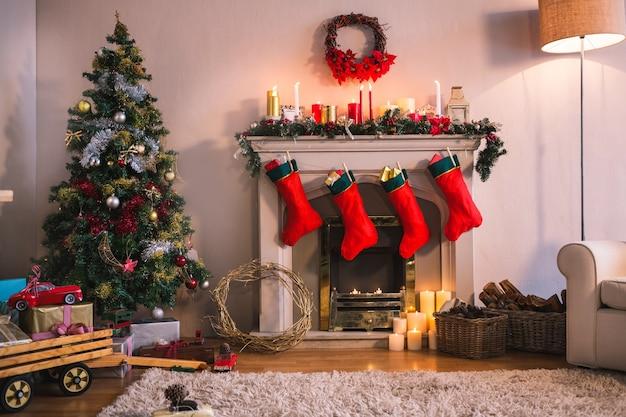 Chimenea con calcetines rojos colgando y un árbol de navidad