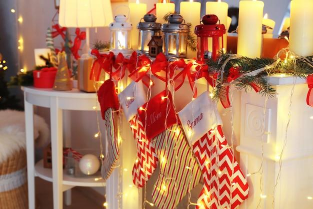 Chimenea decorada con linternas navideñas, velas y calcetines en la habitación