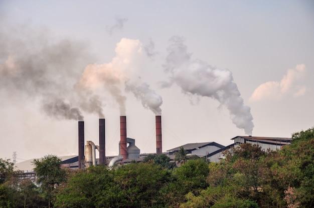 Chimenea industrial con emisión de polución de humo al cielo.