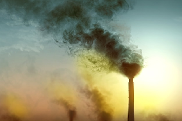 La chimenea produce contaminación del aire por la actividad industrial.