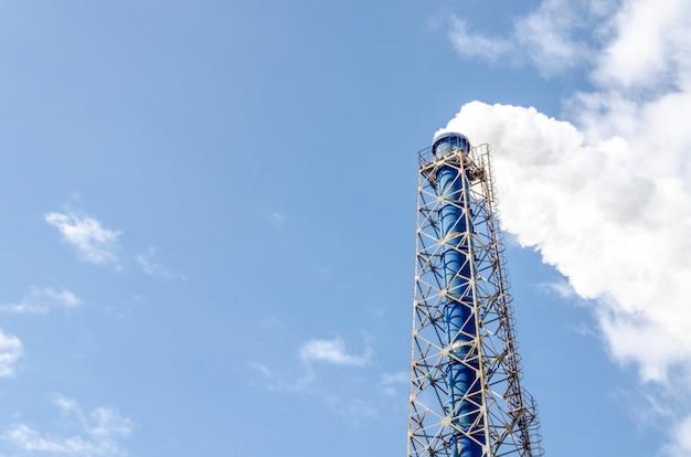 Chimenea y vapor sobre fondo de cielo azul