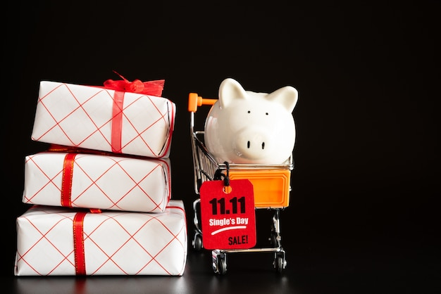 China, 11.11 venta de un solo día, etiqueta de boleto roja colgada en un mini carrito de la compra con hucha