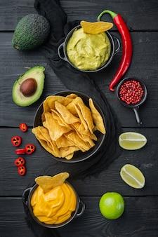 Chip de tortilla de maíz amarillo triangular con salsas, sobre mesa de madera negra, vista superior o endecha plana