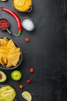 Chip de tortilla de maíz amarillo triangular con salsas, sobre mesa negra, vista superior o endecha plana