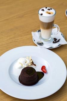 Chips de chocolate servidos con helado y fresa y café con leche de tres capas