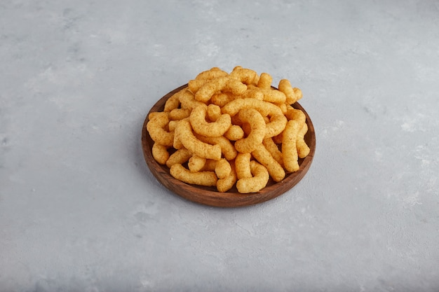 Chips de maíz en especias en un plato de madera, vista superior.