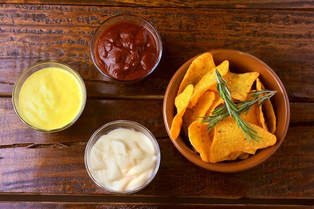 Chips de maíz nachos colocados en un recipiente de cerámica en una mesa de madera junto a salsas variadas