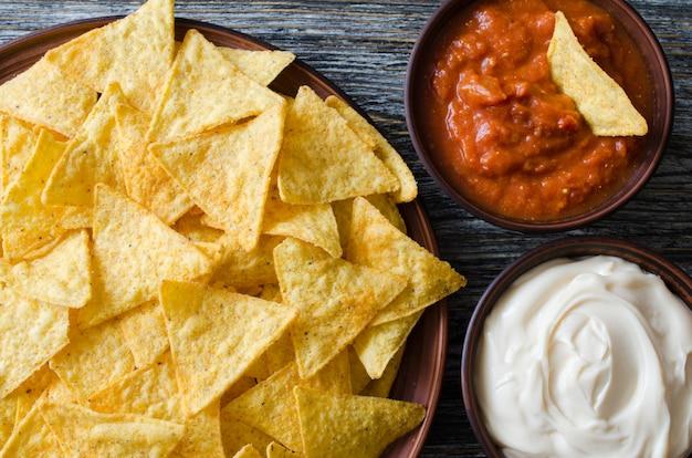 Chips de maíz nachos con salsas picantes de tomate y queso.