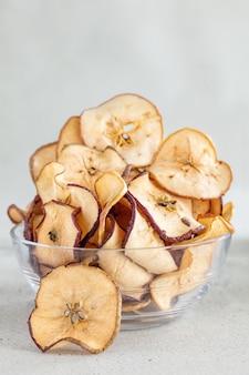 Chips de manzanas secas caídas en un recipiente de vidrio sobre fondo claro