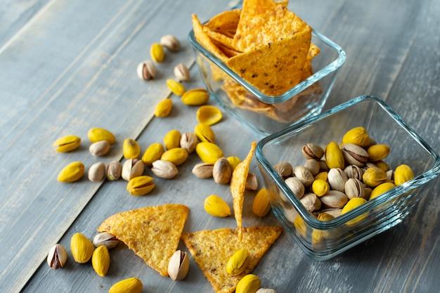 Chips de nachos crujientes y nueces de pistacho saladas y amarillas con azafrán, bocadillos en platos cuadrados de vidrio