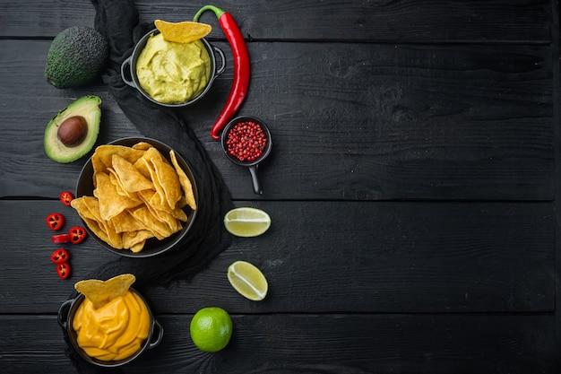 Chips de nachos mexicanos con queso y salsas de guacamole, sobre mesa de madera negra, vista superior o endecha plana