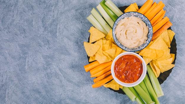 Chips de nachos mexicanos; rodajas de zanahoria con tallo de apio en bandeja con salsa de salsa en un tazón sobre fondo de cemento