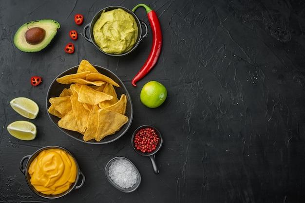 Chips de nachos mexicanos con salsa dip, sobre mesa negra, vista superior o endecha plana