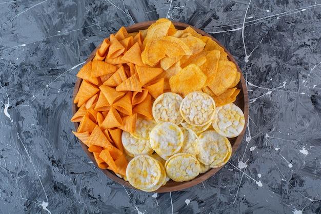 Chips de queso, papas fritas y chips de cono en placa de madera, sobre la superficie de mármol