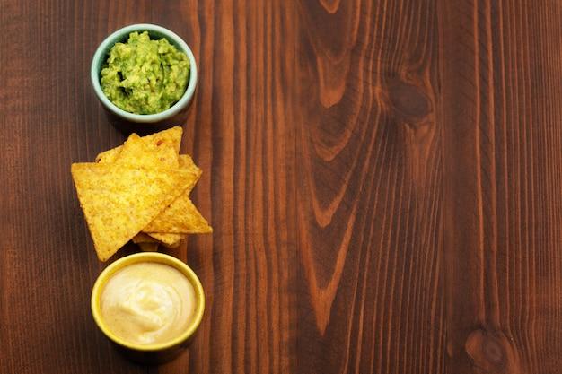 Chips de tortilla nachos, salsa de guacamole y salsa de queso sobre fondo de madera. espacio para texto