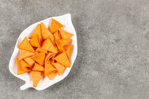 Chips triangulares calientes en un plato blanco.