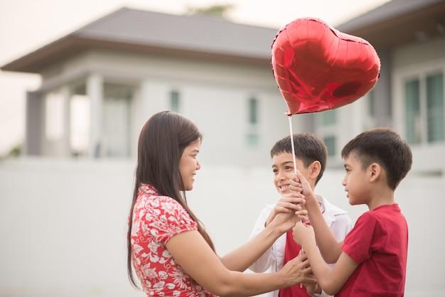 Chiquitos dando corazón de globo a su madre con amor.