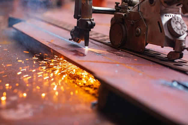 Chispa de corte de metal en la placa de acero del fondo del tanque con destello de luz de corte de cerca en un espacio confinado lateral.