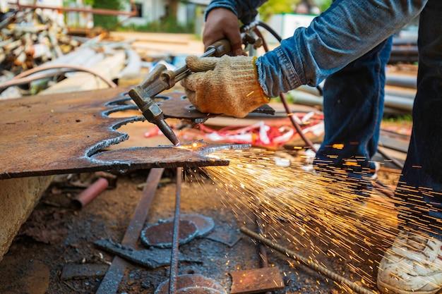 Chispa de corte de metal de trabajador masculino en la placa de acero del fondo del tanque con destello de luz de corte de cerca use guantes protectores de manos.