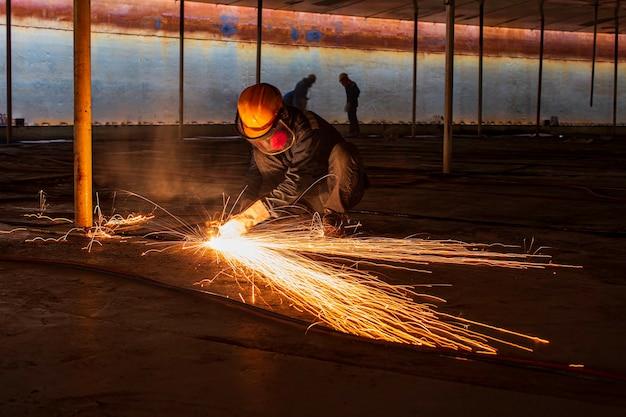 Chispa de corte de metal de trabajador masculino en la placa de acero del fondo del tanque con destello de luz de corte de cerca, use guantes protectores y máscara en el espacio confinado lateral.