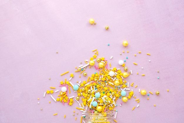 Chispitas de azúcar amarillo granulado sobre fondo rosa closeup plano laico