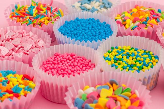 Chispitas de azúcar, decoración para pasteles y helados y galletas sobre fondo rosa